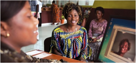 Annie Nyangomba smiles for the camera at Opportunity's new branch in the DR Congo. Bank Teller Alma Romina takes the photo for Annie's ID card as part of the process of opening a biometric-based account.