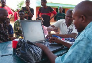 An Opportunity Mozambique loan officer uses Enterprise Open Sky technology to set up accounts for farmers and rural families residing in the bush. Community members.