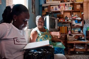 Loan officer Abena Sarpong (pictured left) and Beatrice Boaten look over the Trust Group's membership register in Beatrice's sitting room. (Photo: Sara Joe Wolansky)